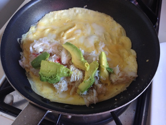 After the eggs are mostly set, add the warm crab and avocado on the half closest to you.